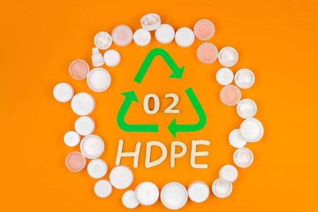 플라스틱 흰색 재사용 가능한 hdpe 병 뚜껑 코드로 재활용 기호 주위에 동그라미에 쌓여있다