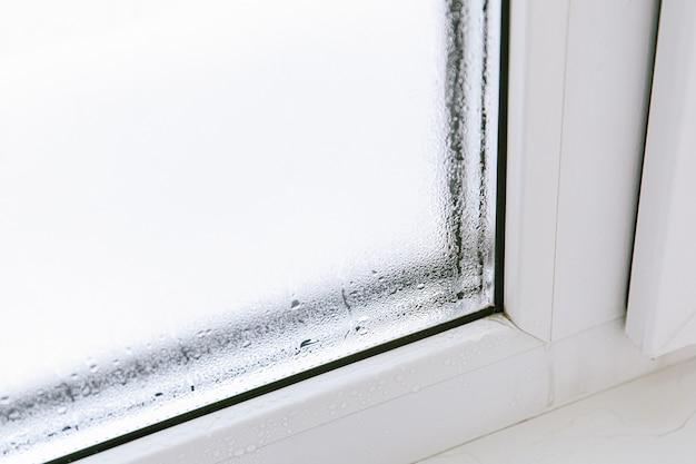 Пластиковое окно с конденсатом влаги и воды на стекле