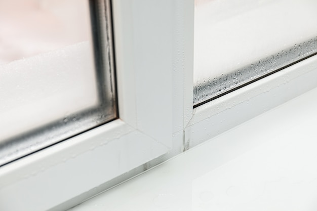 Plastic window with damp and water condensation on glass. bad ventilation in house during cold weather