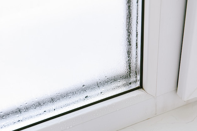Plastic window with damp and water condensation on glass