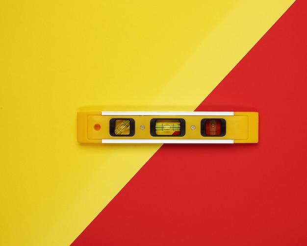 Пластиковый желтый инструмент уровня на двухцветной поверхности