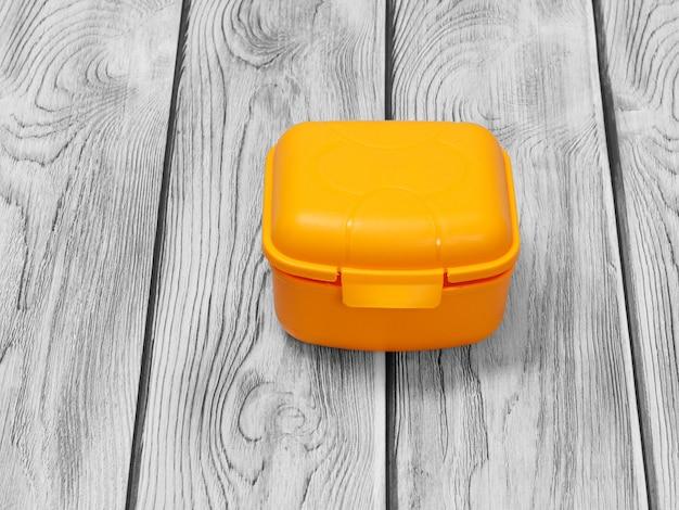 Пластиковый желтый ланч-бокс на деревянных фоне.