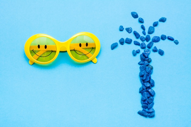 Plastic yellow sunglasses with painted eyes and a smile on the glasses and decorative blue palm-shaped stones