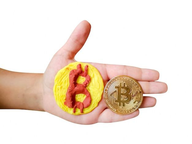 흰색 배경에 격리된 아이의 손에 있는 플라스틱 및 실제 bitcoin 토큰 동전