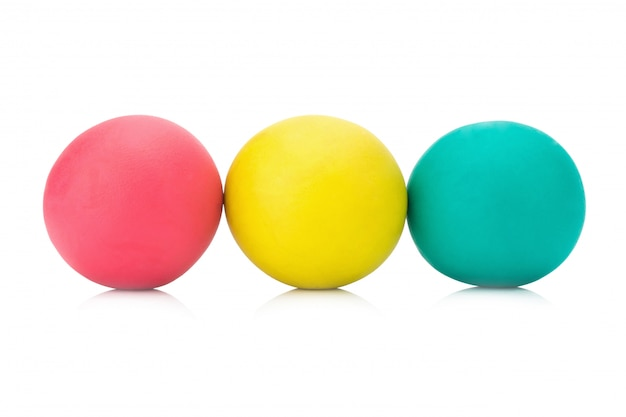 Plasticine clay three red yellow green ball on white background closeup