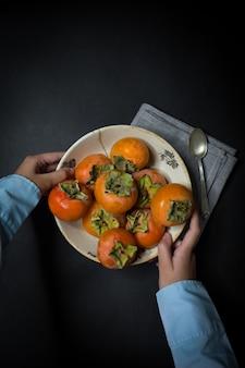 Блюдо с хурмой и руками.