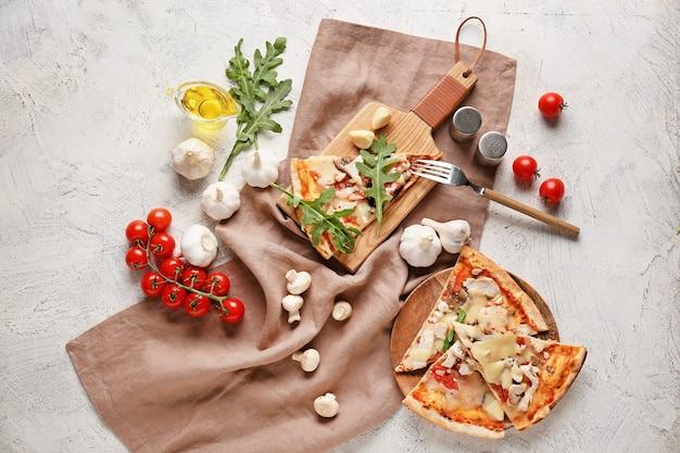 明るい背景においしいピザのスライスとプレートとボード