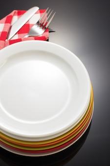 검은 바탕에 냅킨 헝겊에 칼으로 접시와 포크