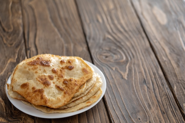 On a plate are fried bread cakes, wooden textured table. with free text, copy space,