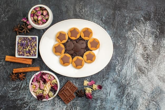 Un piatto di biscotti assortiti con diverse ciotole di fiori secchi e barretta di cioccolato su fondo grigio