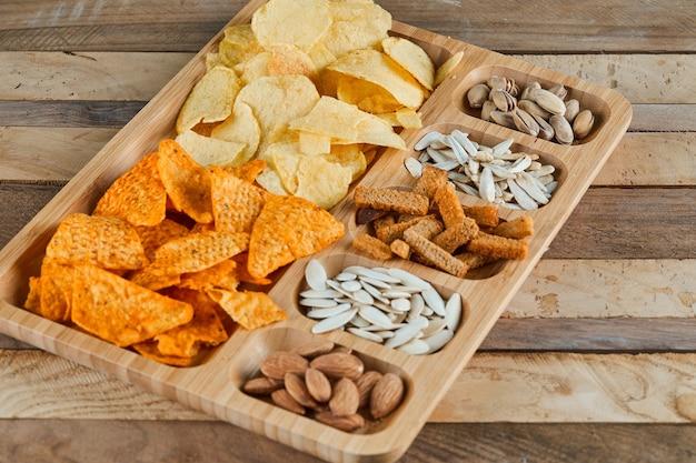 Piatto di snack assortiti su un tavolo di legno. patatine, cracker, mandorle, pistacchi, semi di girasole.