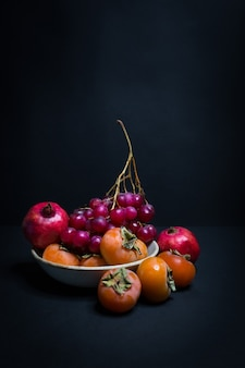 A plate of autumn fruit on a black background