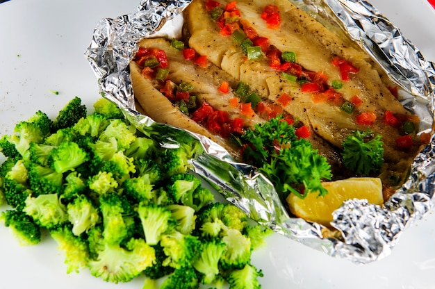 Plate of baked fish in foil with vegetables