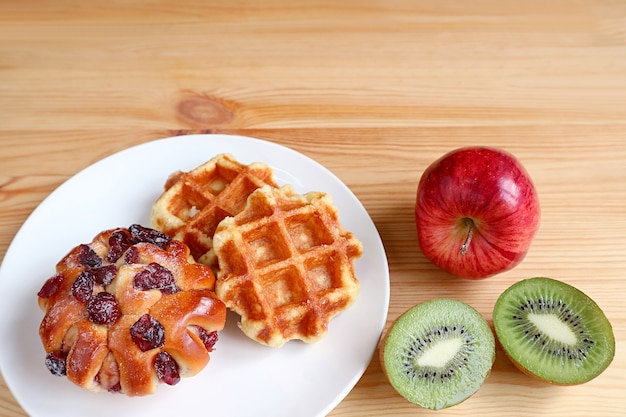 Plate of belgian waffles and raisin bun on wooden table with apple and cut kiwi fruit with copy space