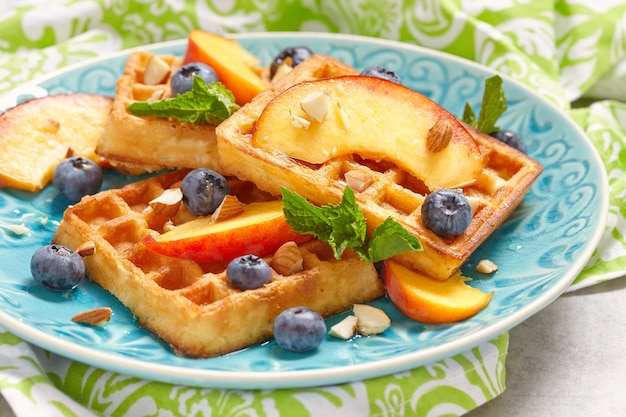 A plate of belgian waffles with fresh fruits