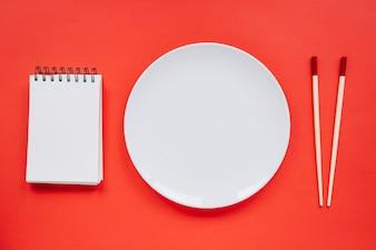 Plate between notebook and chopsticks