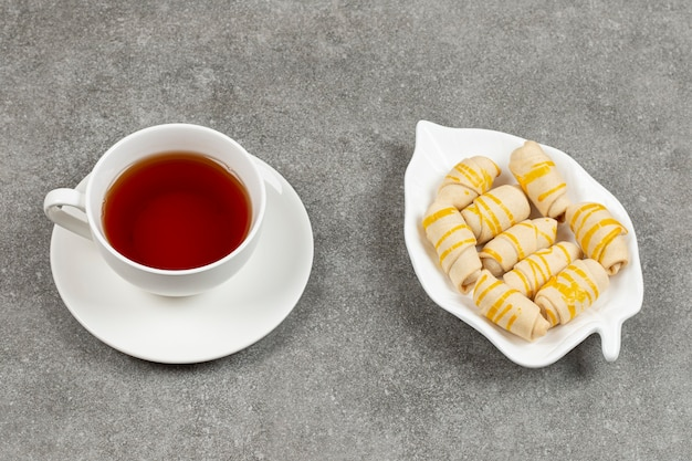 Plate of biscuits and cup of tea on marble surface