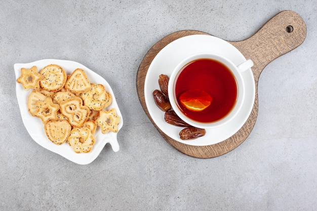 A plate of biscuits and a cup of tea with dates on saucer on wooden board on marble surface.