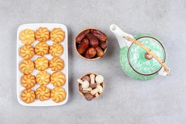 Piatto di biscotti accanto alla teiera decorata e ciotole di datteri e cioccolatini ai funghi su sfondo di marmo. foto di alta qualità