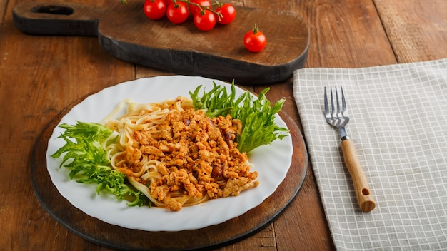A plate of bolognese pasta decorated with herbs on a wooden table next to a gray napkin and a fork. horizontal photo
