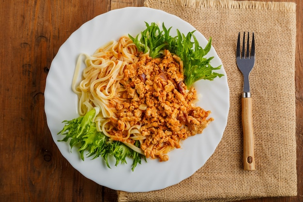 A plate of bolognese pasta decorated with herbs on a wooden table next to a linen napkin and a fork. horizontal photo