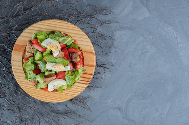Plate of breakfast salad mix on a bunch of branches on marble table.