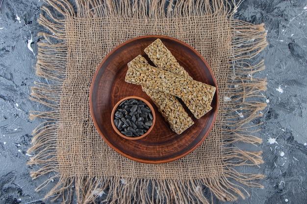 Piatto di caramelle fragili con semi di girasole sulla superficie di marmo.