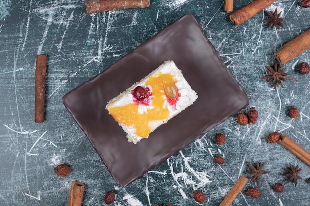 Piatto di torta, cinnamons e chicchi di caffè su sfondo di marmo. foto di alta qualità
