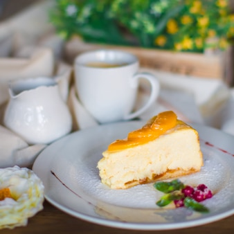 A plate of cheesecake piece garnished with apricot slices