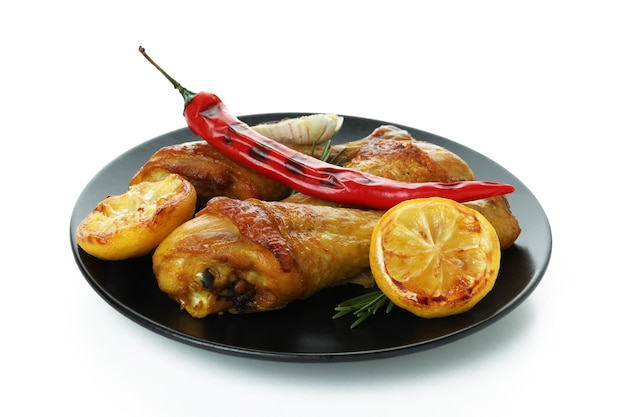 Plate of chicken drumsticks with ingredients isolated on white