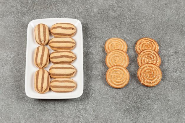 Piatto di biscotti e cracker a strisce di cioccolato sulla superficie di marmo