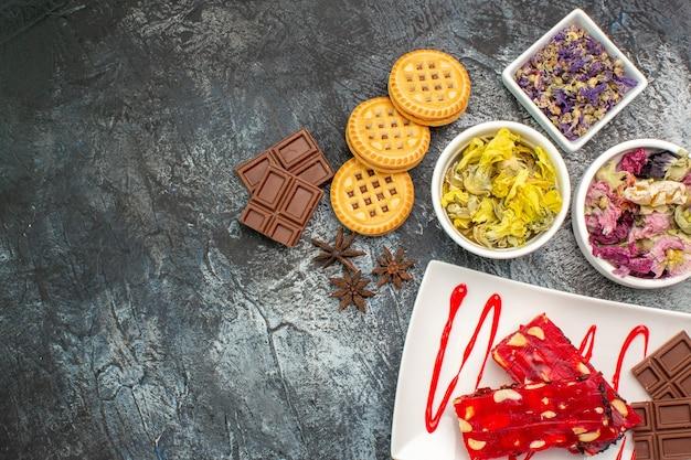 Un piatto di cioccolato con ciotole di fiori secchi e biscotti sul lato destro della terra grigia