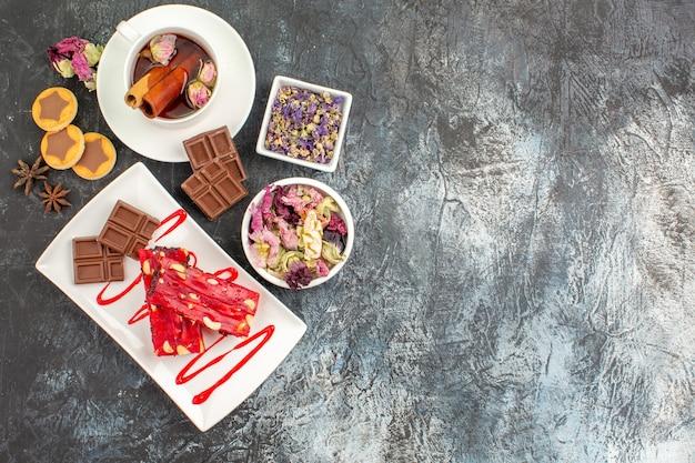 Un piatto di cioccolatini con una tazza di tisana e biscotti e ciotole di fiori secchi su fondo grigio