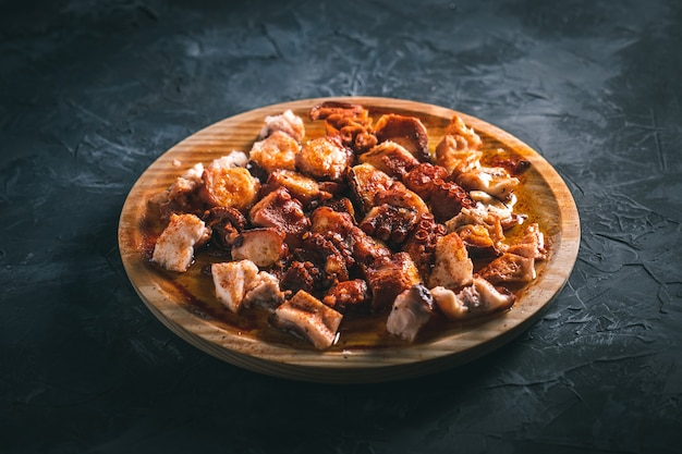Plate of chopped octopus with oil and paprika in a round wooden plate on a dark table