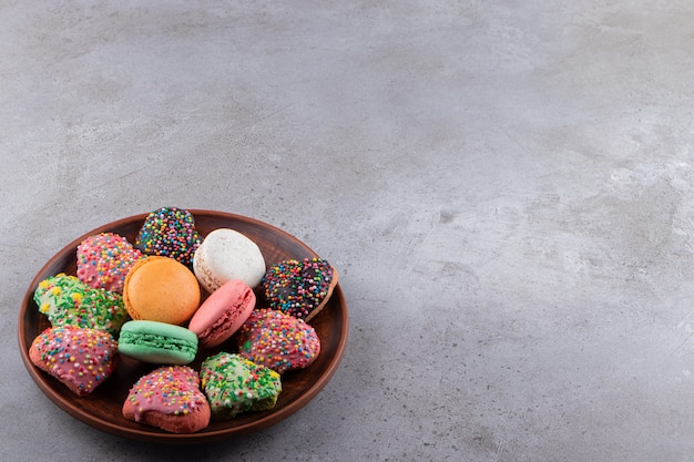 Plate of colorful cookies and macaroons with sprinkles on table.