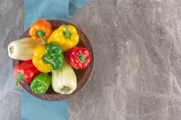 Plate of colorful fresh bell peppers on marble surface