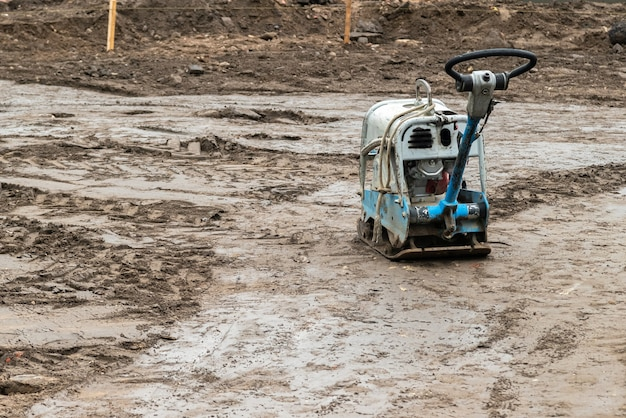 Plate compactor on the ground at construction site.
