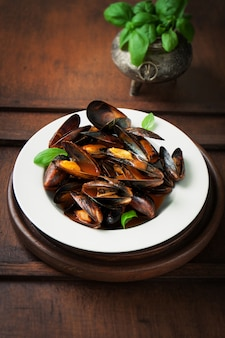 Plate of cooked clams with green leaves