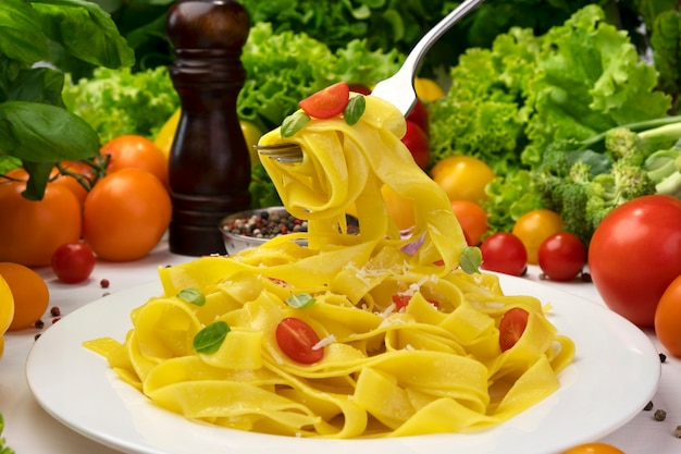 Plate of cooked italian fettuccine pasta, tagliatelle on fork with tomatoes and basil leaves