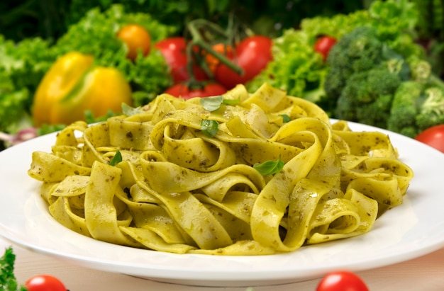 Plate of cooked italian fettuccine pasta with pesto sauce