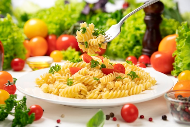 Plate of cooked italian fusilli pasta on fork with tomatoes and basil leaves