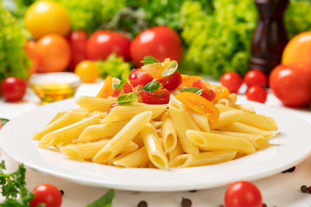 Plate of cooked italian pasta, penne rigate with tomatoes and basil leaves