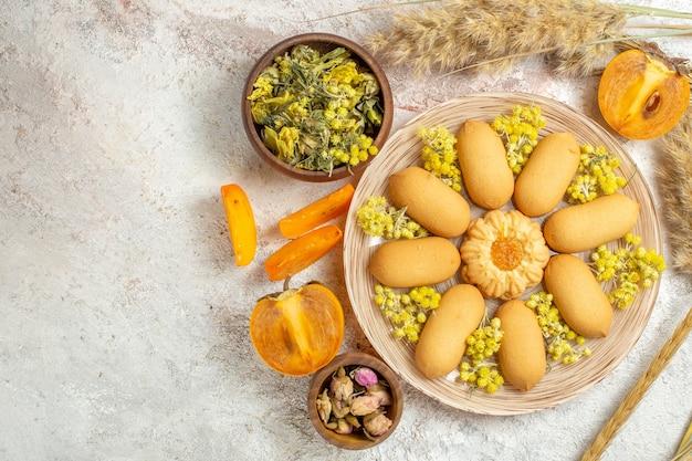 Un piatto di biscotti e ciotole di lavanda secca e fiori, farro e palme su marmo