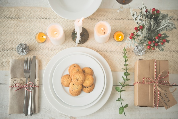 Plate of cookies and present on dinner table with christmas decorations