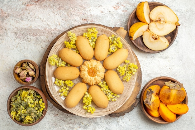 Un piatto di biscotti su un vassoio di legno e frutta e fiori secchi attorno ad esso su fondo di marmo