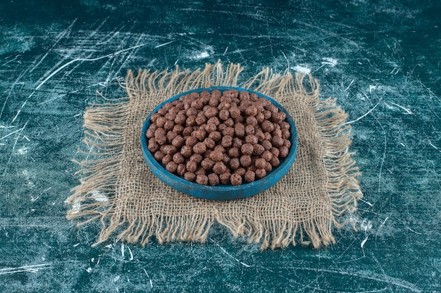 A plate of corn balls on a burlap fabric, on the blue background. high quality photo