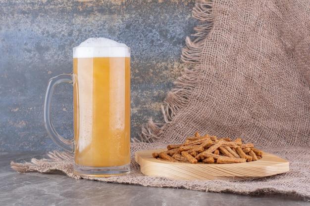 Piatto di cracker con birra sul tavolo di marmo