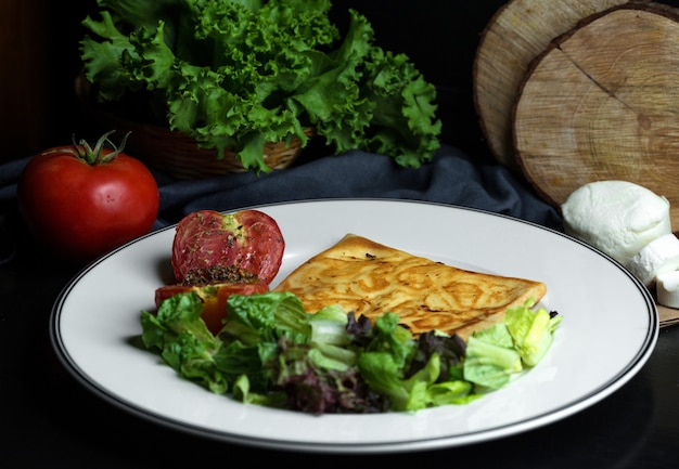 Plate of crepe with cheese served with lettuce salad and grilled tomato