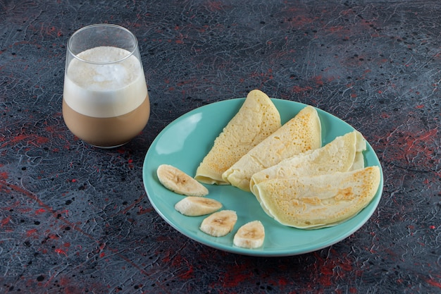 Plate of crepes and sliced bananas with glass of milk coffee on dark surface.