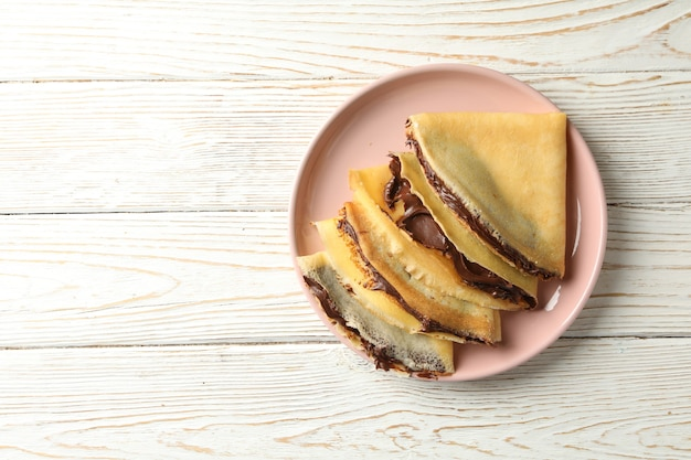 Plate of crepes with chocolate paste on white wooden background